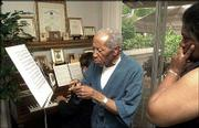 Robert McFerrin, points to sheet music during a music therapy session in his Creve Coeur, Mo., home. At the piano is Jack Jenkins, and McFerrin's wife, Athena McFerrin, listens at right. McFerrin, the father of jazz singer Bobby McFerrin, was the first black man to be signed by the Metropolitan Opera in New York. He suffered a stroke in the late 1980s that impaired his ability to verbalize his thoughts, but he still can sing.