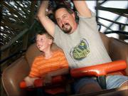 Aaron Girard, 7, left, and his father, Mike Girard, of Wichita, ride the WildCat roller coaster at Celebration City theme park in Branson, Mo. The wooden coaster features an 80-foot drop.