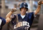 Lawrence's Derek Bailey is greeted at the dugout after scoring on a sacrifice fly in the file photo. Bailey leads the Raiders in several offensive categories this summer and is a big reason why Lawrence won the American Legion Class AAA state championship last weekend.