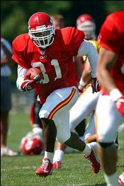 Chiefs running back Priest Holmes carries the ball during practice. Kansas City has four running backs vying to be Holmes' backup in 2003.