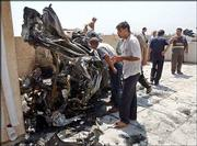 Iraqis view the wreckage of a mini- van that was thrown onto a rooftop next to the Jordanian Embassy in a bomb explosion in Baghdad, Iraq. A massive car bomb exploded outside the embassy Thursday morning, reportedly killing 11 people and wounding many more.
