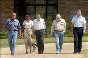 President Bush, left, walks from his ranchhouse to the waiting media with, from left, National Security Adviser Condoleezza Rice, Secretary of Defense Donald Rumsfeld, Vice President Dick Cheney and Joint Chiefs of Staff Chairman Gen. Richard Meyers. They met with the president Friday during his August vacation at his ranch in Crawford, Texas. They are followed by Bush's dog Spot.