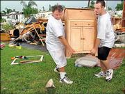 Bob Pobiak, left, gets help from his son Matt Pobiak as they carry a piece of furniture to their van at the A Garden Walk mobile home park in Palm Beach Gardens, Fla. Their home was destroyed Thursday by a tornado.