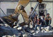 Palestinians watch as a bulldozer works among the rubble of a building destroyed by an explosion during an Israeli army operation in the Askar refugee camp in the West Bank city of Nablus. Israeli troops battled gunmen from the Islamic Hamas group early Friday in a raid on a suspected bomb lab that killed one soldier and three Palestinians after a month of relative calm in the region.