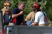 Firefighters carry Pam O'Toole to an ambulance after a single-engine Cessna 182 she was riding in crashed near Topeka. O'Toole's husband, Col. Mike O'Toole, commander of the 190th Air Refueling Wing of the Kansas Air National Guard, died in Friday's crash.