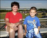 Sarah Narcomey, left, and her son, Justin, 7, both of Lawrence, await the beginning of the demolition derby at the Douglas County 4-H Fairgrounds. The event was Aug. 1.