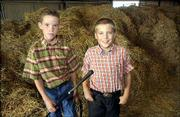 Preston Randall, 10, a member of Meadowlark 4-H Club, left, and Simon Fangman, 9, a member of Clinton Eagles 4-H Club, wait for the start of the livestock auction at the Douglas County Free Fair. Randall was selling a steer and Fangman was selling a sheep Sunday during the auction.
