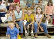 Stacy Burkhart, Baldwin, center, and her children attend the livestock auction at the Douglas County Free Fair. From left are Garrett, 5; Hayden, 4; Stacy; Hunter, 9, and Ramie, 10. Ramie sold her reserve champion meat goat during Sunday's auction.