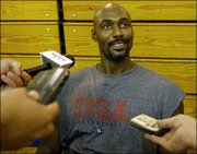 Karl Malone chats with the media after the U.S. Olympic qualifying basketball team's practice. The squad worked out Tuesday in New York.