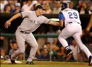 New York first baseman Jason Giambi, left, tags out Kansas City's Mike Sweeney for the final out in the eighth inning. Giambi was forced to tag Sweeney when the throw from third baseman Aaron Boone pulled him off the bag. The Yankees shut out the Royals, 6-0, Tuesday night at Kauffman Stadium in Kansas City, Mo.