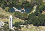 A B-17 passes over Kansas University's memorial Campanile July 21 in conjunction with festivities for the Dole Institute of Politics. The Campanile is a memorial to KU's World War II dead. Potter Lake is in the background.