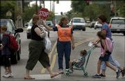 Crossing guard Jan Hurst assists Cordley School students and parents across the busy intersection at 19th and Vermont streets. Hurst is one of 11 Lawrence crossing guards whose positions the city had considered eliminating in this tight budget year.