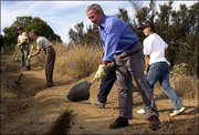 President Bush shovels dirt into the gully of an eroded trail during a tour of the Santa Monica Mountains National Recreation Area in Newbury Park, Calif. Bush's visit Friday focused on his agenda to care for national parks. Working in the background are National Park Service employees and student interns from Woodrow Wilson High School in East Los Angeles.