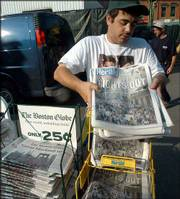 John Dunn sets out his newspapers Friday at Boston's North Station. Most media outlets were able to get the news out despite the blackout.