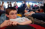 Devin Alberda, 17, of Cleveland, and his sister, Kristen Alberda, right, 20, of New York, watch lines form at a nearby airline ticket counter at LaGuardia Airport. The Alberdas were stranded Friday with thousands of other travelers after the massive blackout that started Thursday afternoon.