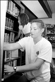 Meghann Maddux and Jen Van Ruyven, St. Catharines, Ontario, help other Kansas University students find employment through the Career and Employment Services office at Burge Union. The pair organized library materials during a cleaning day in July.