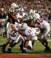 Ohio State tailback Maurice Clarett (13) rushes up the middle against Miami for a five-yard touchdown in the second overtime of the Fiesta Bowl. The Buckeyes won the national championship last season on the run Jan. 3 in Tempe, Ariz.