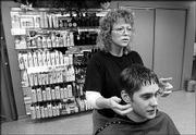 Great Clips stylist Penny Hermann finishes trimming the hair of Bob Johnson, Edmond, Okla., junior. The Great Clips salon is in Kansas Union.