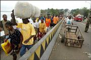 Tens of thousands of hungry, war-weary residents of Liberia's capital continue to cross bridges formerly dividing rebel and government held territories, like this one Saturday in Monrovia. The weeks-old siege had left citizens of the government areas nearly starving while food warehouses in the rebel-held port were heavily looted by residents there.