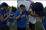 Caleb Skulskie, center, captain of Wattleneck, is doused with water from an ice chest after his team defeated Rudy's Pizzeria 9-8 in the Kaw Valley Kickball League's championship game. Celebrating Sunday in South Park are, from left, teammates Seth Martin, Jonathon Thompson, Skulskie and Noah Martin. Nolan Washatka, a member of The Pig team, is dumping the water. Skulskie was on the phone to a former teammate in Alabama.