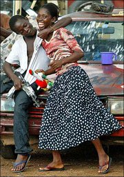 A young rebel who identified himself as Jojo Bad Behaviour, left, playfully hugs a girl he wants to be his girlfriend, in Brewerville near Monrovia, Liberia. Aid has started to arrive in the war-torn country along with West African and U.S. peacekeepers.