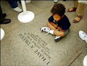 """Andrew Franklin White-Cleary, 4, from Dale City, Va., looks at the words inscribed at the steps of the Lincoln Memorial during the uncovering of a granite landing commemorating the 40th anniversary of Martin Luther King&squot;s """"I Have a Dream"""" speech."""