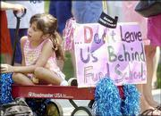 Schwegler School student Jamie Ortiz 6, gets ready to go for a ride during the march for public education funding. At South Park, where marchers gathered, participants listened to speakers call on the Kansas Legislature to adequately fund public schools when they return to Topeka for the 2004 session.