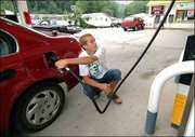 As a safety precaution, Ross Anderson crouches behind his car while pumping gas at Go-Mart in Charleston, W.Va. Residents have been taking extra care after three shootings outside convenience stores in the past two weeks.