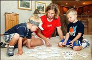 Mary Tilger, a survivor of West Nile virus, plays a card game with her sons, Adam, left, 3, and Shane, 4, at their Broomfield, Colo., home. Tilger, 32, is among the more than 500 Coloradoans who contracted the virus this year, according to officials.