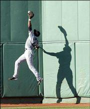 Seattle center fielder Mike Cameron leaps but is unable to make a catch on Kevin Millar's game-winning double in the 10th inning. The Red Sox defeated the Mariners, 7-6, Saturday in Boston.