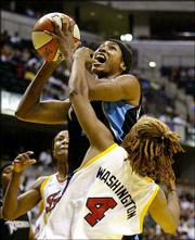 Cleveland center Pollyanna Johns Kimbrough, center, is fouled by Indiana guard Coquese Washington. The Fever beat the Rockers Saturday in Indianapolis.