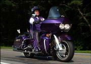 "Bonnie Kiefer, 62, from Portsmouth, R.I., rides her 2002 Harley Davidson Road Glide during a ride with fellow ROMEO (Real Old Motorcyclists Eating Out) members. Kiefer is part of a growing number of folks who are spending their golden years grinding pavement in a motorcycle rather than in an RV. Her Harley, decked out in purple and silver accouterments, is called ""Pegasus."""
