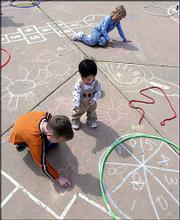 Michael Nguyen, age 1, offers a piece of chalk to Erik Keil, 8, as he and his twin sister Ashlyn Keil draw pictures on the ground.