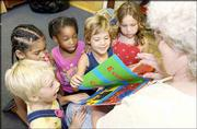 New York School kindergartners, from left, Jai Strecker, Makyla Brady, Raemona Wilson, Sophia Minder and Emily Basks read a book with the help of substitute teacher Darlene Henning. Like last year, Monday's half-day session marked the difference from the 2000-2001 school year, when kindergarten was a full-day program at the school.