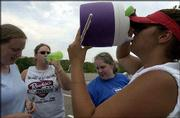 Kansas University marching band piccolo players hydrate themselves during band practice at the west campus practice field. From left are Alison Koelper, Shawnee freshman; Lindsey Kinkelaar, Dodge City junior; Cassie Golden, Overland Park freshman; and Jenny Jaimes, Overland Park sophomore. The marching band practiced Wednesday in 100-degree weather. Forecasters predict temperatures to top off in the 80s for Saturday's season football opener at Memorial Stadium.