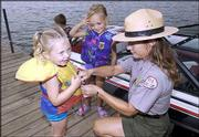 Bunnie Watkins, natural resources management specialist at Perry Lake, helps Hailey Engelke, 3, left, and Morgan Kubick, 3, both of Perry, during a water safety demonstration. Recreation officials stressed safety Thursday before the long Labor Day weekend.