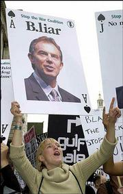 A member of the Stop The War Coalition holding a giant playing card like those used by the U.S. forces to depict members of Saddam's regime protests outside the Royal Courts of Justice in London. British Prime Minister Tony Blair, pictured on the card, testified Thursday as part of a hearing on the death of British weapons expert David Kelly.