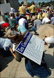 Demonstrators pray outside the Frank M. Johnson Federal Court Building in Montgomery, Ala. The protesters marched Thursday from the state judicial building to the federal court. They were praying for the return of a Ten Commandments monument to the state judicial building's rotunda. It was moved from that location Wednesday.