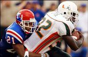 Miami running back Frank Gore (32) is tackled by Louisiana Tech free safety Michael Johnson. The third-ranked Hurricanes cruised in their season opener, 48-9, Thursday night in Shreveport, La.
