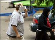 Jeffrey Lee Parson, 18, left, holds papers in front of his face to shield himself from the media as he and an unidentified person enter the garage to Parson's home in Hopkins, Minn. The high school senior was arrested Friday for allegedly launching a worldwide computer virus and was later released under restrictions set by a federal judge.