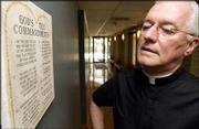 The Rev. Vince Krische, director of St. Lawrence Catholic Campus Center, looks at a replica of the Ten Commandments hanging in the Catholic campus center's hall. Lawrence clergy have been following a conflict in Montgomery, Ala., in which Chief Justice Roy Moore refused to back down from a judge's order to remove a granite monument of the Ten Commandments from public view.