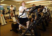 Ellen Lipschitz, foreground, a scientist at Hoffmann-La Roche pharmaceutical company, works out on an elliptical trainer at the company fitness center in Nutley, N.J. Lipschitz has lost 93 pounds and lowered her blood pressure through exercise.