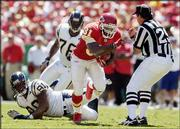 Kansas City running back Priest Holmes (31) avoids a collision with umpire Steve Wilson, right, as he gets past San Diego's Adrian Dingle (90) and Dequincy Scott for a gain of eight yards. Holmes scored two touchdowns in the Chiefs' season-opening 27-14 victory Sunday in Kansas City, Mo.
