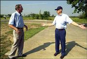 John Houck, left, and Hank Pichler discuss plans to rebuild a civic center and post office in Franklin. The men last week talked about the post office, which once stood where the flag in the background flies. It was destroyed by a tornado that struck the small southeast Kansas town May 4.