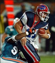 Dolphins defensive end Adewale Ogunleye, left, sacks Buffalo QB Drew Bledsoe.