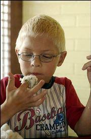 Sushi is proving to be popular with Lawrence residents of all ages. William Ruhe, 6, gets ready to eat a sushi roll at Sushi Station.