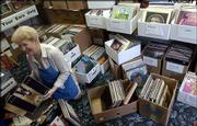 Janis Hutchison sorts through some of the 6,000 record albums and 10,000 compact discs that will be on sale this weekend for the benefit of Kansas Audio-Reader Network. As Hutchison perused the donated items Monday, she found early Beatles, Frank Sinatra and Glenn Miller vinyl LPs.