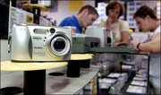 Kodak digital cameras are on display at Best Buy in Syracuse, N.Y. Eastman Kodak Co. slashed its $1.80 annual dividend to 50 cents a share. The move, announced Thursday, is aimed at reducing spending and boosting investment in digital markets by as much as $3 billion.