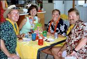 From left, Duane and Leann Dickson and Susan and Bud Stagg, all of Lawrence, visit during the River City Cosmopolitan Club's 2003 Inaugural Luau. The club is affiliated with the Cosmopolitan International organization, which aims to find a cure for diabetes.