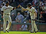 San Francisco's Barry Bonds, left, is congratulated by teammate Benito Santiago after Bonds scored on a double by Edgardo Alfonzo in the eighth inning. The Giants knocked off Florida, 2-0, in Game 1 of their National League Division Series playoff game Tuesday in San Francisco.